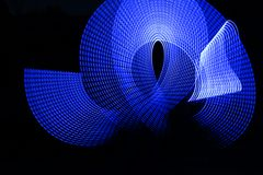 Blue electric light painting, long exposure photography, ripples and waves pattern against a black background. Blue electric Light Painting Photography, parallel royalty free stock photos