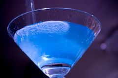 Blue Electric Martini. A blue raspberry martini being poured into a large martini glass royalty free stock images