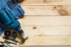 Blue electric power drill with set of bit and blue jeans on grug. E wooden  plank background top view with copy space Royalty Free Stock Photo