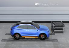Blue electric SUV car in battery swapping station. Pack of batteries on the left side of the car.  3D rendering image Royalty Free Stock Photo