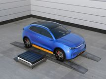 Blue electric SUV car in battery swapping station. Pack of battery module on the right side of the car.  3D rendering image Royalty Free Stock Photography