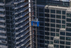 Blue elevator at a high-rise building construction site. Blue elevator on the wall of a high-rise building at a construction site Royalty Free Stock Images
