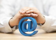 Blue email symbol protected by hands Royalty Free Stock Photography
