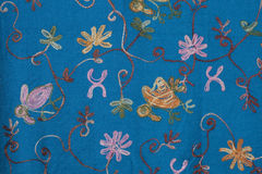 Blue embroidered floral fabric background. Blue indian fabric background with embroidered floral design stock images