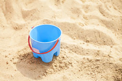 Blue empty bucket with red handle on sand Royalty Free Stock Image