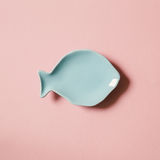 Blue empty fish shaped dish on pink background. Flat lay Royalty Free Stock Photos
