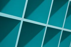 Blue empty plastic shelves with shadow. S and glares. Turquoise colored racks Royalty Free Stock Photography