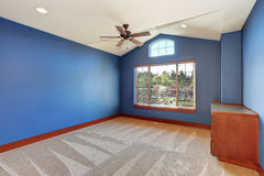 Blue empty room with vaulted ceiling and carpet floor. Stock Photos