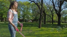 1 blue En tonårs- flicka i en parkera som spelar med bubblor Sinnesrörelser av en tonåring i natur arkivfilmer