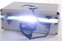 Blue Energy Case With Open Lock. Silver brief case slightly open with bright blue light coming out in a burst of energy from the case. Open handcuff on top of stock photos