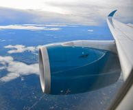 Blue engine of passenger airplane. In the sky with cloudscape background stock photography