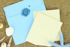 Blue envelope on the beach. Paper card and blue envelope on the beach stock images