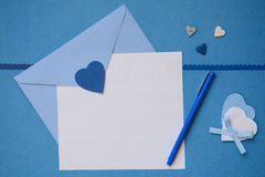 Blue envelope and white blank paper with some crafts Stock Image