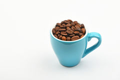 Blue espresso cup full of coffee beans over white Stock Photography