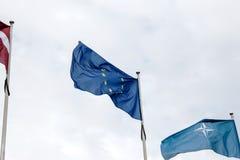 Blue European Union and NATO flags on a foggy sky background. European Union flag, NATO and Latvia flags on a wind. Foggy sky stock photos