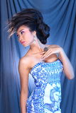 Blue Evening Gown Ball Dress in Asian beautiful woman with fashion make up black hair. Studio lighting blue drape fabric background light behind, portrait stock photography