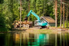 Blue excavator clears the shore of the lake Royalty Free Stock Photo