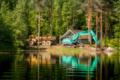 Blue excavator clears the shore of the lake Royalty Free Stock Image