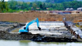 Blue excavator in construction site. In tilt shift, look like miniature Royalty Free Stock Image