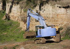 Blue excavator digging Stock Images
