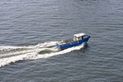 Blue Excursion Boat Cutting Through Bay Stock Photography