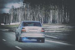 Blue exhaust gases emanating from an old car moving along the road against stock photos