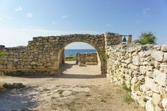The blue expanse of the black sea is visible through the arch in the ancient wall. Chersonese royalty free stock images