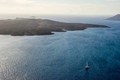 Blue expanses of the Aegean Sea with a ship and a volcano. View from Santorini stock photo