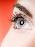 Blue eye. On red background (shallow DoF stock photography