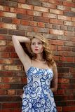 Blue eye Beauty. Blue eyes blue dress girl against brick wall Royalty Free Stock Photo