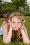 Blue eye beauty. Girl laying on the Grass with red shoes, red lipstick Stock Photography