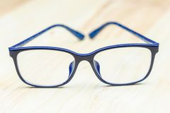 Blue eye glasses on wood table for business, education concept design stock photo