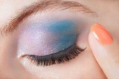 Blue eye smokey make up, beauty. Blue eye smokey make up with finger with orange nail polish Stock Photos