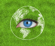 Blue eye surrounded by a drawing of the Earth. Over grass texture Stock Photography