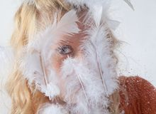 Blue Eye of Teen Through White Feathers Royalty Free Stock Photography