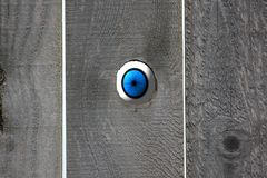 Blue Eyeball Looking In Through Knot Hole In A Wooden Fence. royalty free stock image