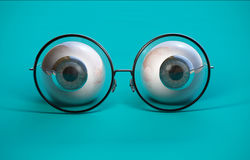 Blue eyeball and round glasses stock image