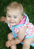 Blue eyed baby. Girl sitting on the grass Stock Images