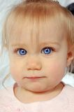 Blue Eyed Baby. An adorable baby with big blue eyes wearing pink Royalty Free Stock Images