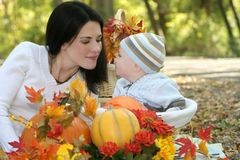 Blue Eyed Baby Boy in Basket, Fall Theme. Portrait of a blue eyed baby boy in a basket outdoors, surrounded by fall leaves and flowers, in a park setting stock images