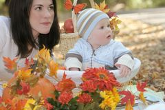 Blue Eyed Baby Boy in Basket, Fall Theme. Portrait of a blue eyed baby boy in a basket outdoors, surrounded by fall leaves and flowers, in a park setting stock photography