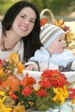 Blue Eyed Baby Boy in Basket, Fall Theme. Portrait of a blue eyed baby boy in a basket outdoors, surrounded by fall leaves and flowers, in a park setting royalty free stock photos