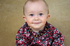 Blue eyed baby girl in floral shirt smiling Stock Photos