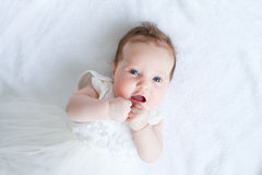 Blue eyed baby girl in a white dress. Beautiful blue eyed baby girl in a white dress Royalty Free Stock Images