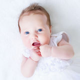 Blue eyed baby girl in a white dress Stock Image