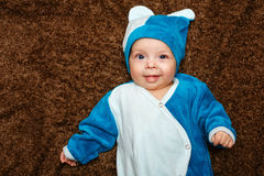 Blue-eyed baby. Lies on his back and smiling while looking at the camera Stock Photography