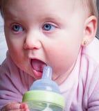 Blue-eyed Baby sucking bottle Stock Photo