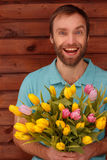 Blue-eyed bearded man with flowers on wood background. Blue-eyed bearded man with flowers happily smiling against a background of brown wooden boards Stock Photos