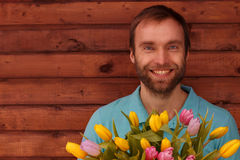Blue-eyed bearded man with flowers on wood background. Joyful blue-eyed bearded man with a bouquet of yellow tulips Stock Photography
