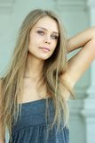 Blue-eyed beautiful girl. Beautiful woman standing against wall in background Royalty Free Stock Photo